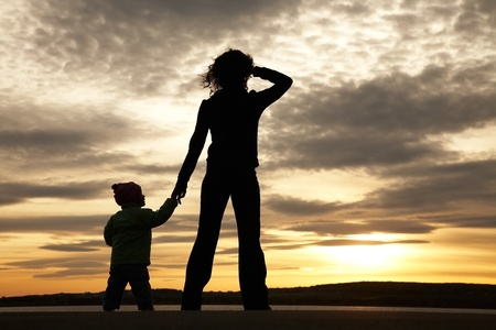 Silhouette of mother and baby looking away into the sunset and water photo