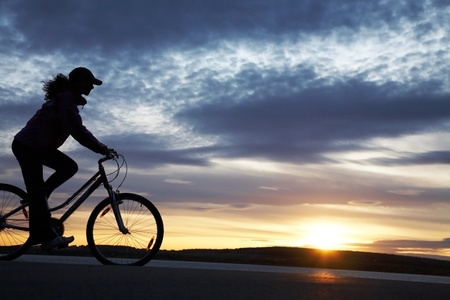 The beautiful girl is cycling on seacoast on a sunset Stock Photo - 8936346