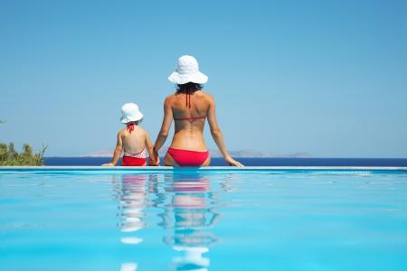 Junge Mutter mit Baby Tochter sitzt am Rand des Pools und starre auf das Meer