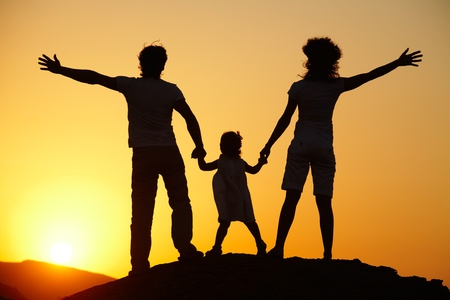outdoor activities: Silhouette of a young family with a child standing on a decline against the bright sun Stock Photo