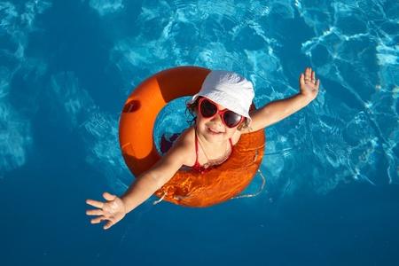 summer fun: Funny little girl swims in a pool in an orange life preserver