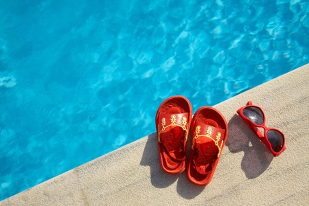 Colored flipflops  and sunglasses by the swimming pool photo