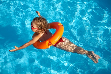water play: Funny little girl swims in a pool in an orange life preserver