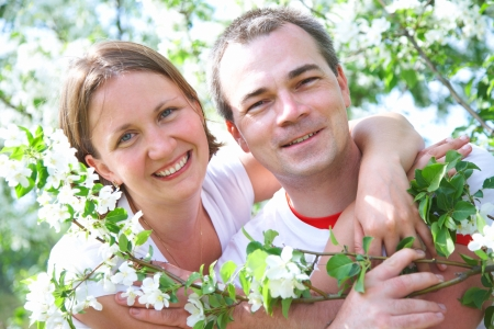 Happy Mature couple having good time in the spring garden. Blooming apple orchard photo