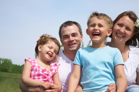 family lifestyle portrait of a mum and dad with their two kids having fun outdoors photo
