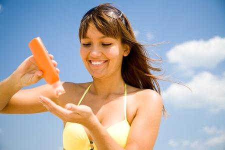 beautiful young woman in bikini smear protective cream on the skin on the beach under the sun Stock Photo - 9131928