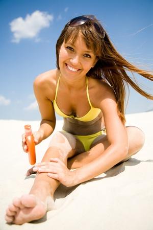 beautiful young woman in bikini smear protective cream on the skin on the beach under the sun Stock Photo - 9131915