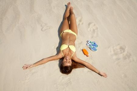 beautiful young woman in bikini lying and sunning on the beach under the bright sun Stock Photo - 9132485