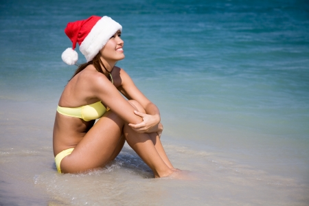 beautiful young woman in a bikini and hat of Santa Claus sitting in the water at the seaside resort photo