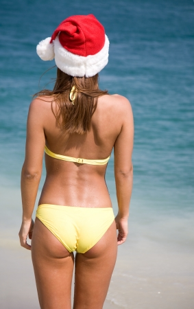 beautiful young woman in  bikini and hat of Santa Claus enters to sea photo