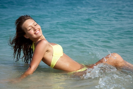 beautiful young woman in bikini lying down and smiling in sea at the resort photo