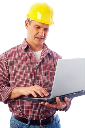 handsome man-builder in helmet examining on a laptop on a white background  photo