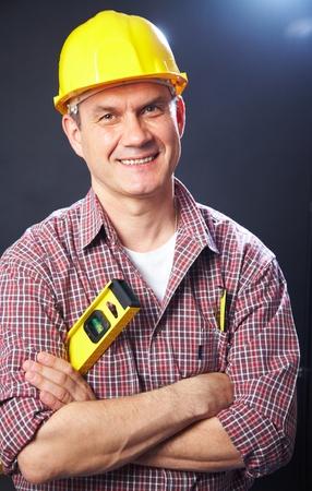vertical portrait of a smiling handsome man-builder on a dark background photo