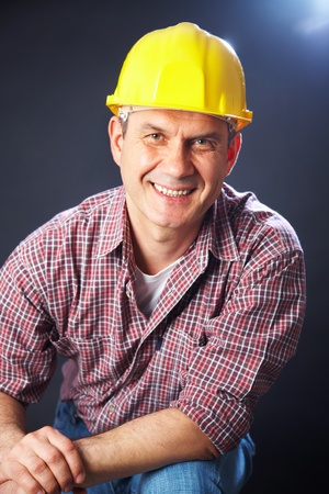 vertical portrait of a smiling handsome man-builder on a dark background photo