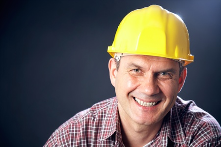 horizontal portrait of a smiling handsome man-builder on a dark background photo