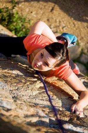 clamber: La bella ragazza � impegnata in arrampicata su roccia su una roccia verticale