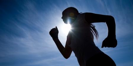 marathon running: Female runner silhouette against the blue sky and sun Stock Photo