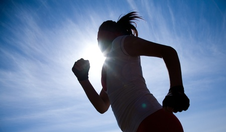 Female runner silhouette against the blue sky and sun Stock Photo - 9131660