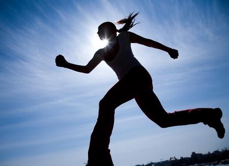 Female runner silhouette against the blue sky and sun photo