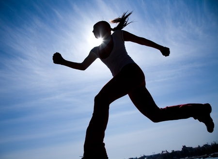 fast train: Female runner silhouette against the blue sky and sun Stock Photo