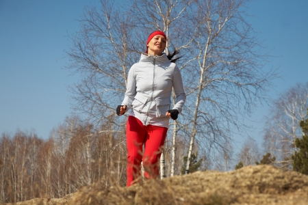 Beautiful young  woman jogging cross country photo