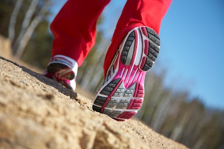 the sole of the shoe: Close-up legs of a girl jogging on the wood
