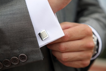 A man fastening a cuff-link before getting married  photo