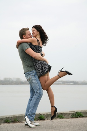 A pair of beautiful young people embracing and kissing on the embankment of the river photo