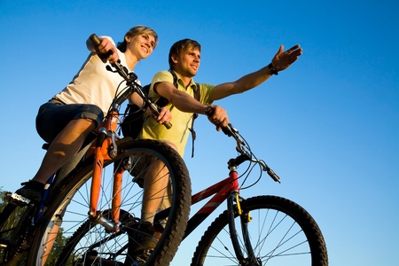 adventure sports: Beautiful Couple on bicycles on the brink of a rock and look afar from rock breakage