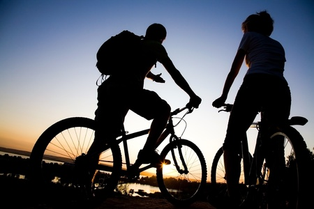 breakage: Beautiful Couple on bicycles on the brink of a rock and look afar from rock breakage