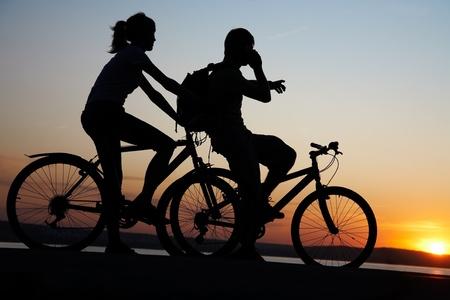 ciclista: Bonita pareja en bicicleta al borde de una roca y lejos de la rotura de la roca