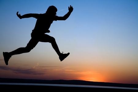 personas corriendo: Joven corriendo a lo largo de la orilla del mar al atardecer Foto de archivo