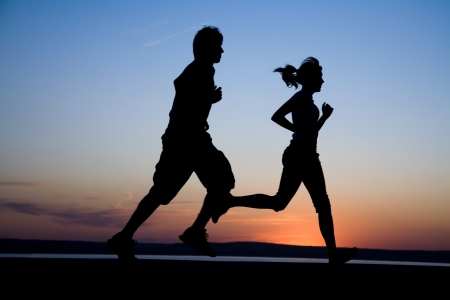 hombres corriendo: El hombre y la mujer ejecutar�n juntos en una puesta de sol en la costa del lago