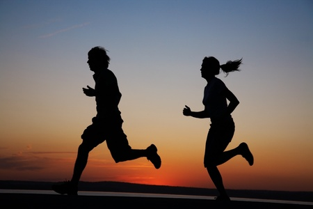 The man and the woman run together on a sunset on lake coast Stock Photo - 9131730