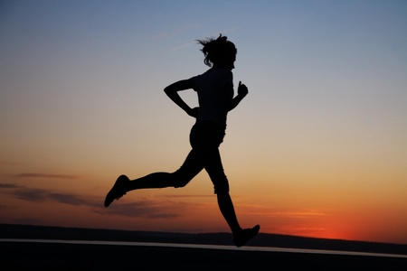 sprint:  Young Female runner silhouette against the sunset