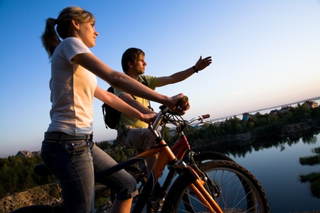 Beautiful Couple on bicycles on the brink of a rock and look afar from rock breakage  photo