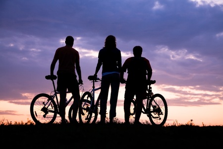 Silhouette of three cyclists on the background of a beautiful sunset photo