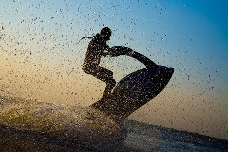 water jet: strong man jumps on the jetski above the water at sunset .silluet. spray.