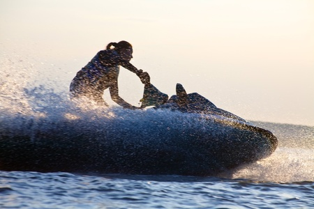 jet skier: beautiful girl riding her jet skis in the sea at sunset. silluet