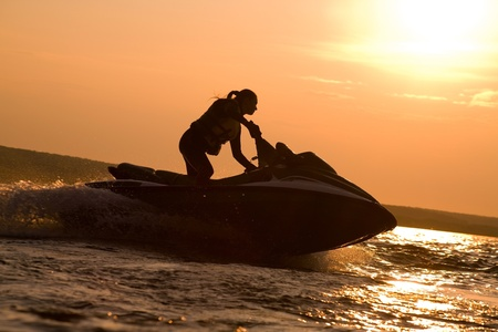 jet skier: beautiful girl riding her jet skis in the sea at sunset .spray