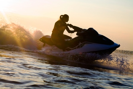 jet skier: beautiful girl riding her jet skis in the sea at sunset. silluet. spray