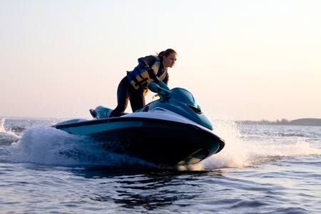 water jet: beautiful girl riding her jet skis in the sea at sunset. spray