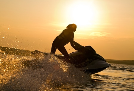 beautiful girl riding her jet skis in the sea at sunset . spray photo