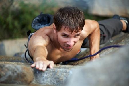 escalando: Foto del joven subiendo la roca