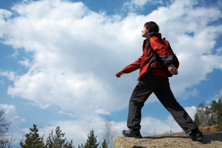 young male traveler is walking through the mountains on the background of the beautiful sky photo