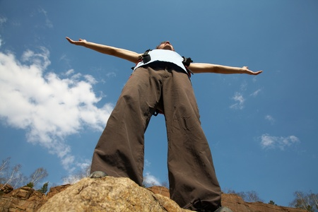 Climber reaches his arms up, standing on a stone at the top of his route, over a deep blue sky.  photo