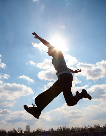 Young man is jumping against cloudy sky  Use it for lifestyle concepts Stock Photo - 21606616
