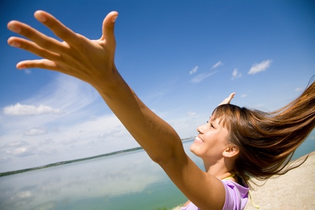 girl blowing: beautiful young woman opened her hands with delight at the blue sky Stock Photo