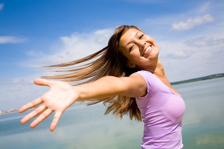 blowing wind: beautiful young woman opened her hands with delight at the blue sky Stock Photo