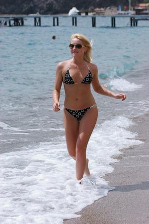 Sexy woman in bikini running along the sea coast,  photo